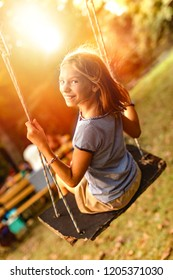 Happy laughing child girl on swing in sunset summer