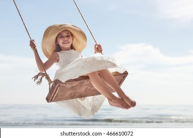 Happy laughing child girl on swing in summer day