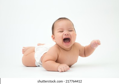 happy laughing child lies on stomach, 5 months old asian baby boy