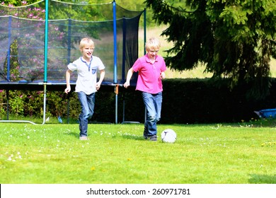 Happy laughing children, twin teenage boys, playing soccer in the garden at the backyard of the house on sunny summer vacation day