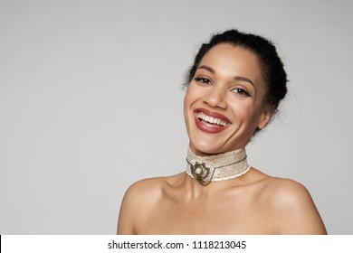 Happy laughing closeup portrait of beautiful mixed race woman wearing chocker looking at camera, isolated on gray background