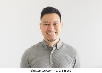 Happy and laughing face of ordinary Asian man in grey shirt. Concept of charming laugh.