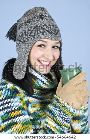 8032e8dee836f8 Happy laughing female teen in winter clothes holding a hot drink to heat up  over blue