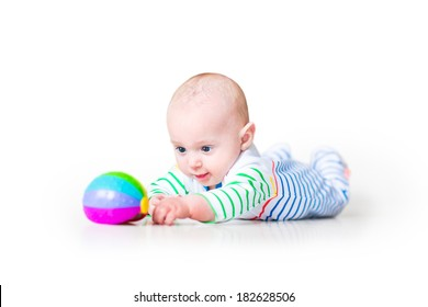 Happy laughing funny baby boy wearing a colorful shirt learning to crawl playing on his tummy, on white background