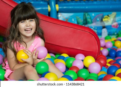 Happy laughing girl kid having fun at indoor play center. Child playing with colorful balls in playground ball pool. Holiday