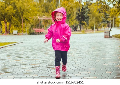 happy laughing girl in a pink raincoat and rubber boots joyfully runs in the rain along the alley of the autumn park. go walk in the rain
