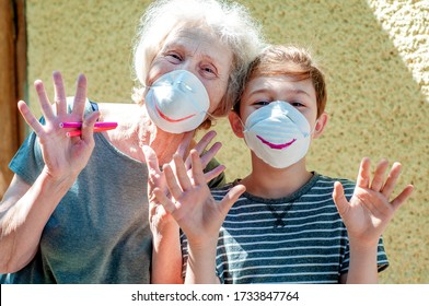Happy laughing grandmother with grandchild in a respiratory masks plays together near house. Family fun. Stay at home. Drawing a smile on protective masks. Quarantin, isolated. Coronavirus covid-19.