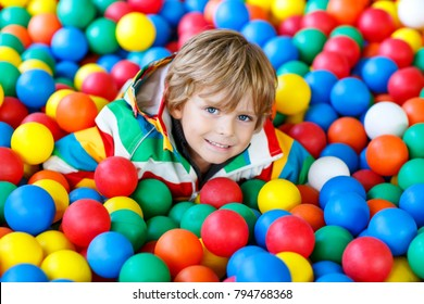 Happy laughing kid boy having fun in ball pit on birthday party in kids amusement park and indoor play center. Little child playing with colorful balls in playground ball pool.
