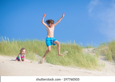 Happy laughing kids, school age boy and funny curly toddler girl, brother and sister, playing on a beach,jumping in sand dunes enjoying vacation on a sunny summer day on North Sea, Holland
