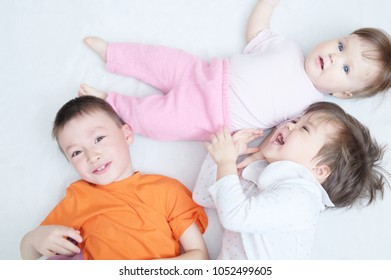 happy laughing kids, three children different ages lying, portrait of boy, little girl and baby girl, happiness in childhood of siblings, living in big family with three children