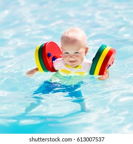 Happy laughing little baby boy playing in outdoor swimming pool on a hot summer day. Kids learn to swim. Child with colorful floaties. Swimming aid for kid. Family vacation in tropical resort