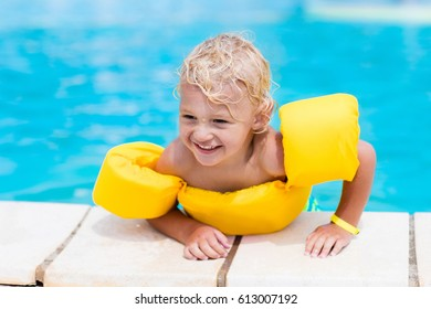 Happy laughing little boy playing in outdoor swimming pool on a hot summer day. Kids learn to swim. Child with colorful floaties. Swimming aid for kid. Family vacation in tropical resort