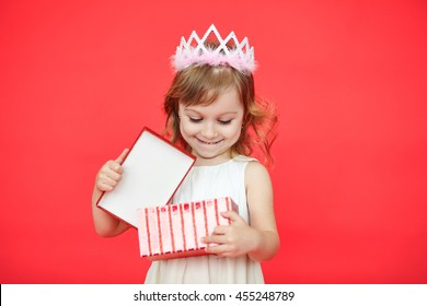 Happy laughing little girl, adorable toddler in a white dress, holding birthday present, opening box decorated with bow, excited and surprised