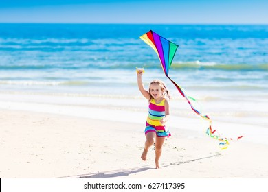 Happy laughing little girl flying a colorful kite running and jumping in sand on beautiful tropical beach during active summer family sea vacation. Kids play on ocean shore. Child with beach toys
