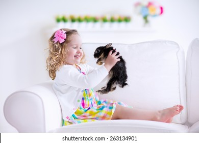 Happy laughing little girl playing with a baby rabbit, hugging her real bunny pet and learning to take care of an animal. Child on a white couch at home or kindergarten.