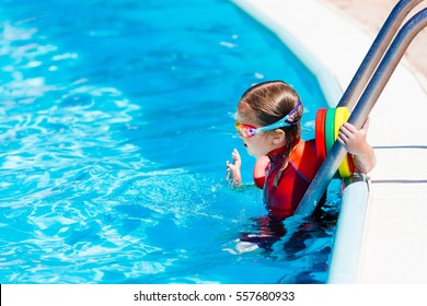 Happy laughing little girl playing in outdoor swimming pool on a hot summer day in sun protection rash guard. Kid in goggles and UV safe bathing suit learning to swim with colorful floaties