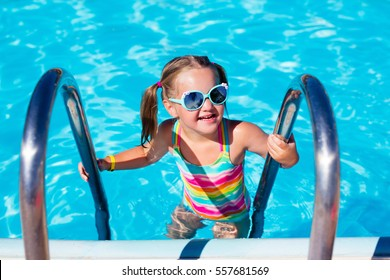 Happy laughing little girl playing in outdoor swimming pool on a hot summer day. Kid in colorful bathing suit and goggles learning to swim in tropical resort. Water fun for children