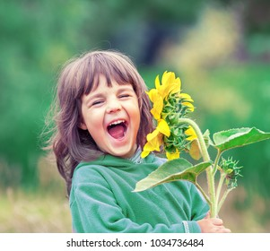 Happy laughing little girl with sunflower outdoors in summer