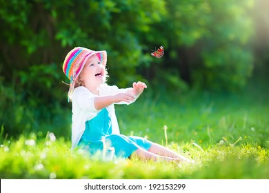 Happy laughing little girl wearing a blue dress and colorful straw hat playing with a flying butterfly having fun in the garden on a sunny summer day