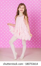 happy laughing little long hair girl dancing on pink background