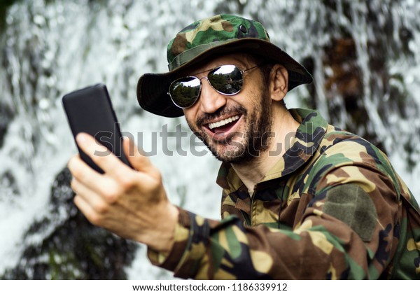 The happy laughing man in military pattern is using phone and making selfie in nature with waterfall.
