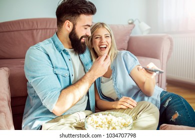 Happy laughing modern young couple enjoying at home