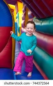 Happy laughing redhead toddler bounce in a colorful trampoline