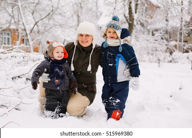 Happy laughing toddler boy in a beautiful snowy winter forest on Christmas day