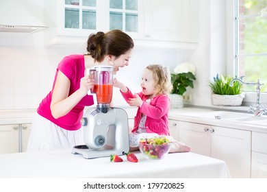 Happy laughing toddler girl and her beautiful young mother making fresh strawberry and other fruit juice for breakfast together in a sunny white kitchen with a window