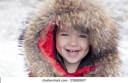 Happy laughing toddler girl wearing a fur jacket in red while playing and running in a beautiful snow day