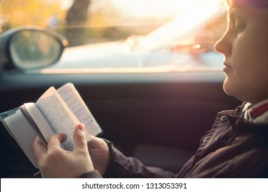 Happy, laughing woman travel and dreaming by car with sunlight, holding notebook of your dreams, plans, goals, experiences, ideas, lived emotions and feelings. Life balance concept lifestile.