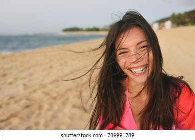 Happy laughing young Asian woman enjoying day at the beach on summer vacation. Healthy living natural beauty multiracial girl smiling with hair in the wind, tanned skin having a good time.