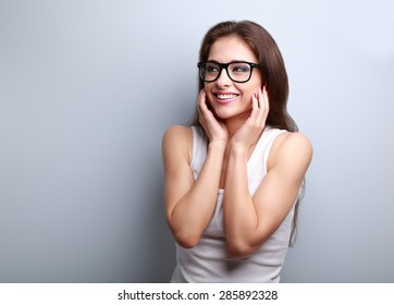 Happy laughing young casual woman holding hands the face on blue background with empty copy space