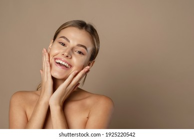 A happy laughing young woman with perfect skin, natural make-up and a beautiful smile. Female portrait with bare shoulders on a beige background