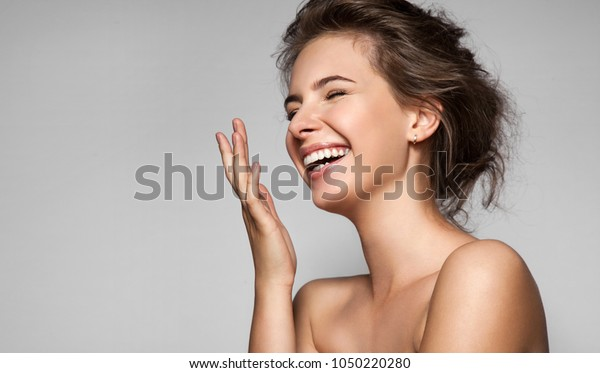 A happy laughing young woman with perfect skin, natural make-up and a beautiful smile. Female portrait with bare shoulders on a gray background