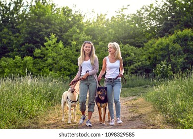 Happy laughing young women walking their dogs along a grassy rural track in spring together sharing a joke