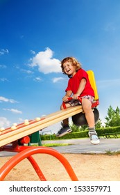 Happy lauging little three years old child sitting on the seesaw