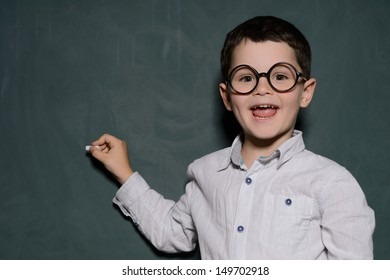Happy learner. Cheerful little schoolboy in glasses standing near the blackboard and smiling