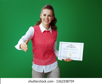 happy learner woman with Certificate of Graduation giving hand for handshake isolated on chalkboard green background. Image include fake Certificate made for  illustrative purposes