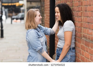 Happy lesbian couple chatting in the street