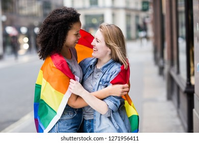 Happy lesbian couple with a LGBT flag