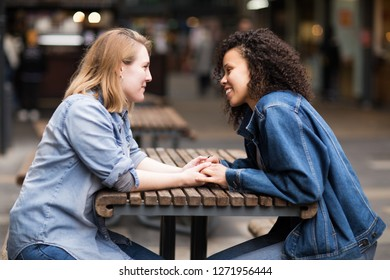 Happy lesbian couple sitting together talking