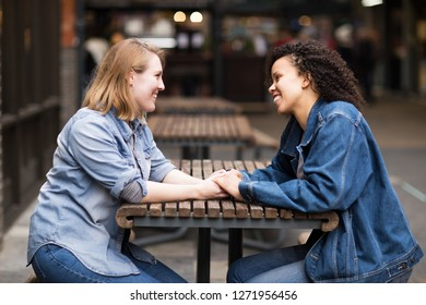 Happy lesbian couple sitting together chatting