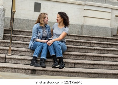 Happy lesbians sitting on a step in the city