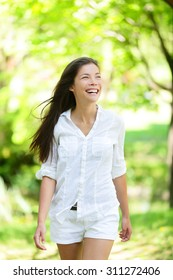 Happy life. Healthy woman walking in spring summer park looking away doing a health walk wearing white cotton or linen casual clothing. Mixed race Asian / Caucasian young female in her 20s.