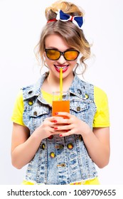 Happy Life Ideas and Concepts. Upbeat and Happy Caucasian Blond Girl With Orange Juice and Straw. Wearing Denim Vest and Sunglasses. Against White. Vertical Shot