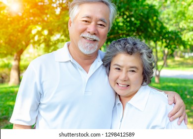 Happy life and long lived concept. Handsome old man and beautiful old woman embracing together, look at camera. Older couple have good health and get happiness because they look after their self well