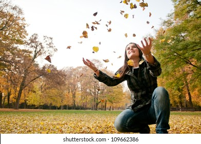 Happy life - woman throwing leaves in fall