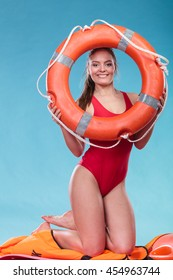 Happy lifeguard with ring buoy lifebuoy. Woman girl supervising swimming pool water on blue. Accident prevention.