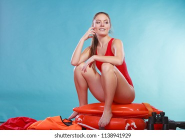 Happy lifeguard sitting on rescue tube buoy and ring lifebuoy. Joyful woman girl having fun. Accident prevention and rescue.